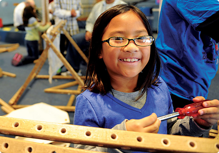 A young girl smiles as she uses real Skyline Tool Box tools to build.