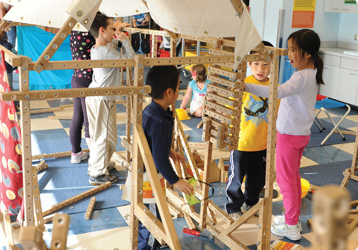 A group of 4 children work together to build a wooden structure with Skyline Tool Box materials.