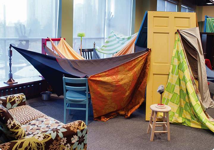 Blankets drape over chairs, couches, doors, and tables to create a large scale fort.