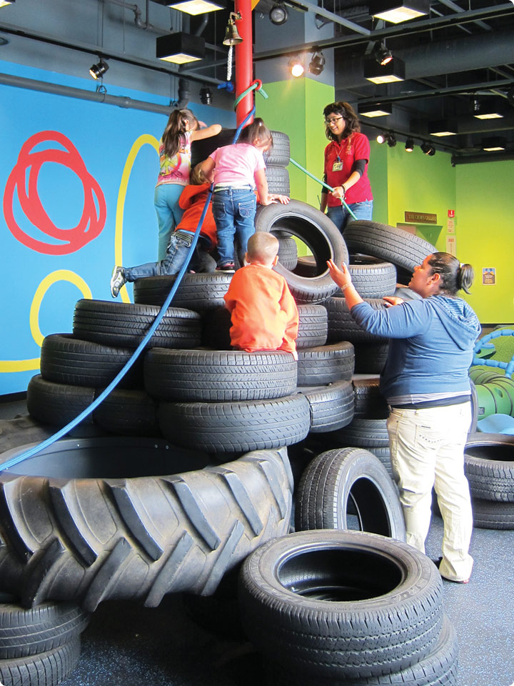 Children make their way up a giant stack of tires.
