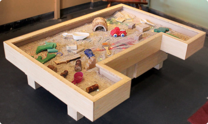 A box filled with shimmering sand, shovels, and other toys is ready for toddlers to explore.