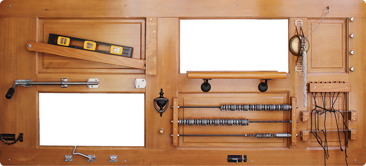 A brown wooden door is outfitted with levels, strings, screws, and washers for little ones to experiment with.