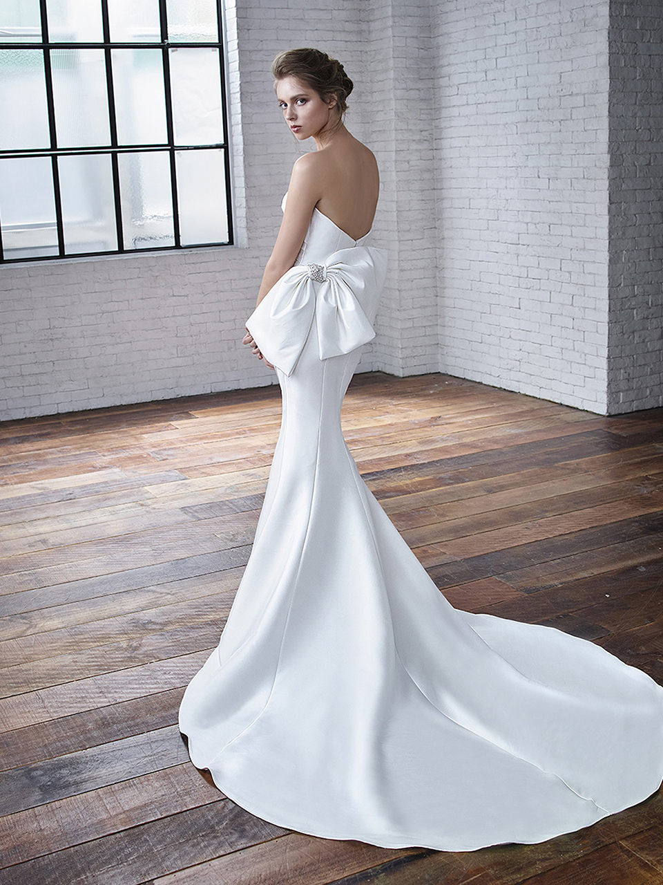 Carmen:  This is a very sophisticated style. The fabric is a stretch Mikado, allowing the gown to beautifully form to the bride's silhouette. The ruched bodice is accented with a gorgeous bow finish off this classic look!
