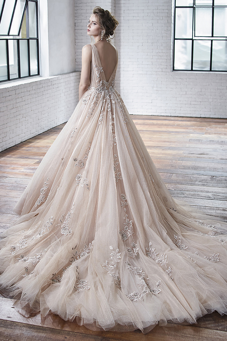 Cheryl:  This ballgown is a bridal fairytale come true! The gathered bodice and skirt are made all the more beautiful with the glitter tulle and beaded embroidered lace. This gown will surely sweep you off your feet!