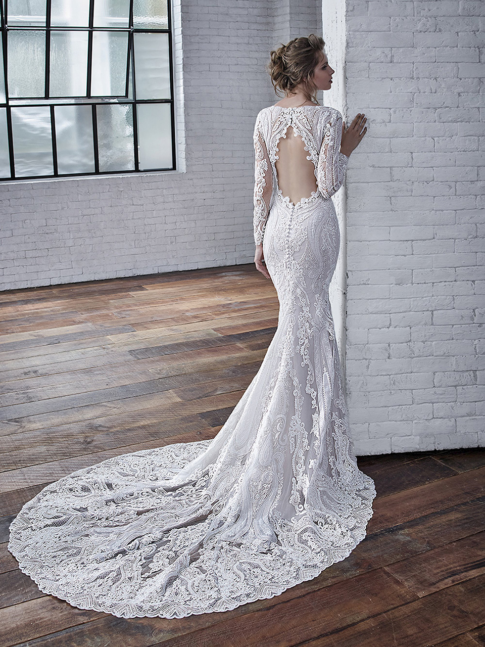 Callista:  This stunning fit and flare beautifully blends a corded lace with embroidered lace, giving the gown gorgeous dimension. The three-quarter sleeves and key-hole back emphasize the classic nature of this beauty.