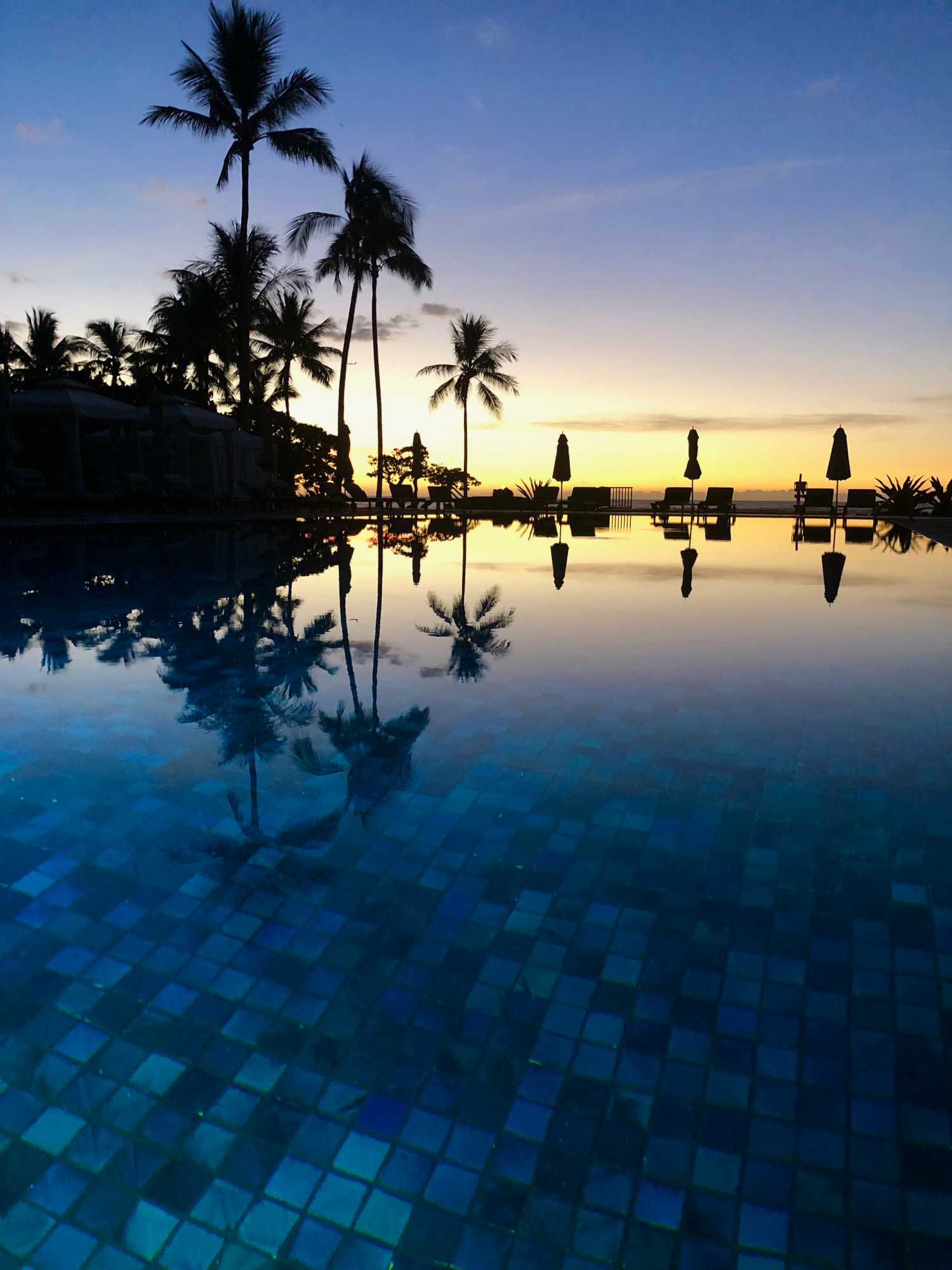 sunset over the pool at the Four Seasons Resort Hualālai