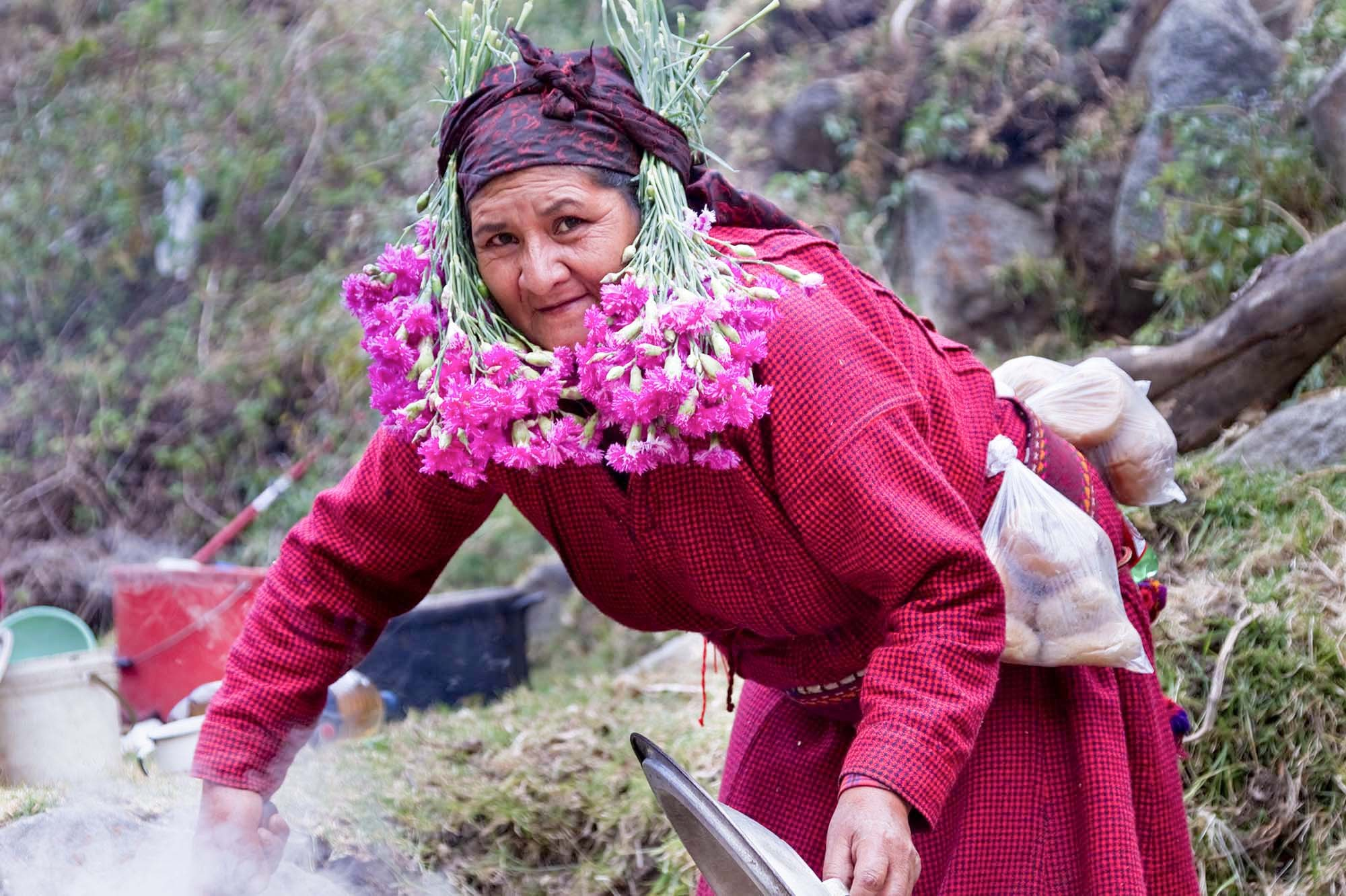 To clean and prepare the soil for sowing  (amrutzpta) ,  the owner of the farm invites friends and family members to help.  The  owner wears flowers and cooks a large meal for everyone.  The following  days, the owner returns the favor and helps at someone else's farm.   Clorinda Ramirez is cooking today!