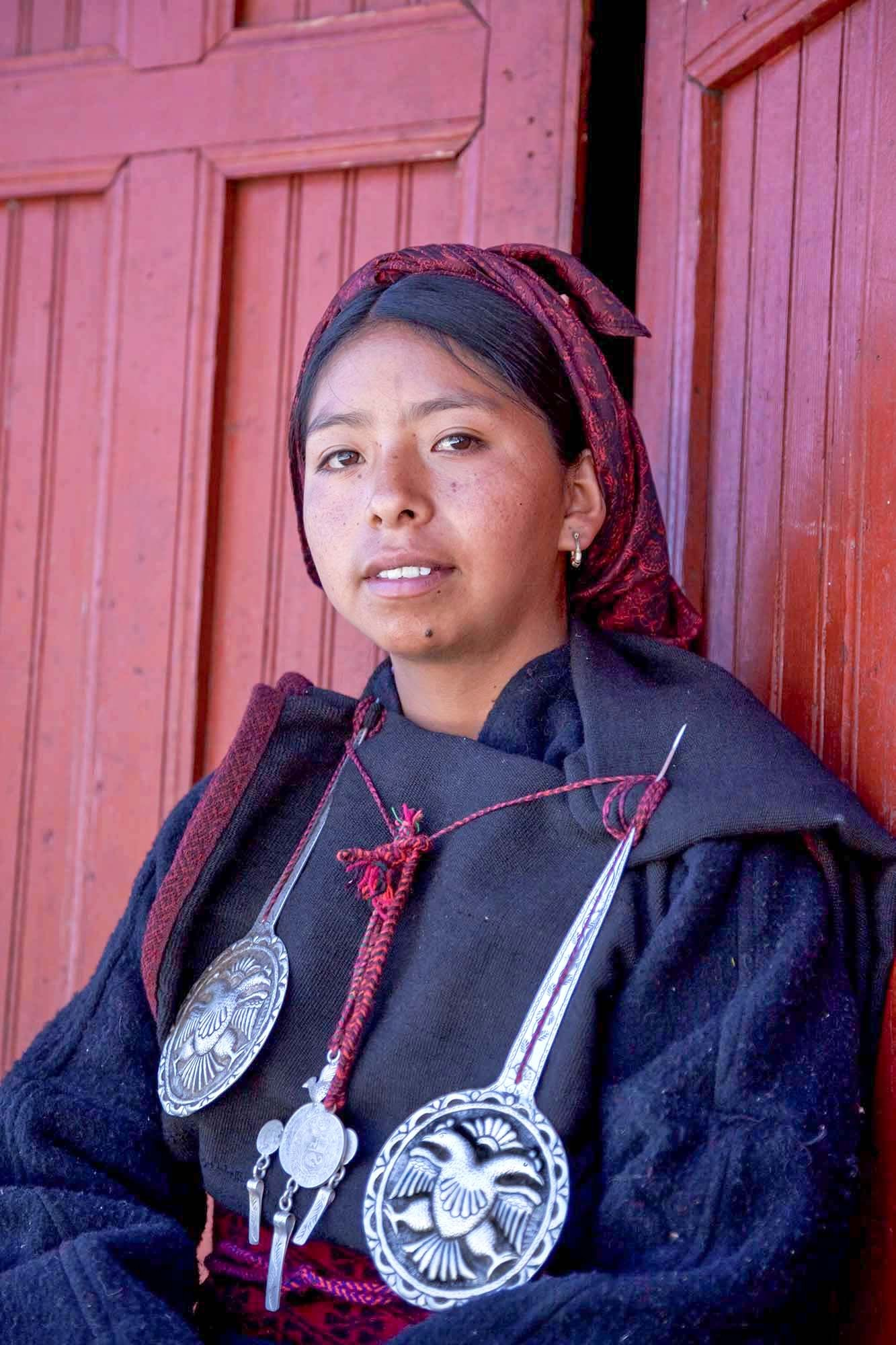 """Katty wearing the old traditional outfit during an official function in Tupe.  The original outfit is made of alpaca wool.  The  urku  consist of three rectangular pieces that are pinned to outside of the  kutuna .  The  kutuna  is made of a lighter wool in a form of a long gown.  A colorful woven border is added to the  urku .  During mourning, the border changes to a sober color to show that they are sad.    This outfit it's always worn with two large silver pins with eagle figures called  p""""itx""""u .  The  urku  are attached to the  katuna  with the  p""""itx""""u .  The  p""""itx""""u  are held in place with a woven thread from which  piñi , made of some old silver Peruvian coins, hang."""