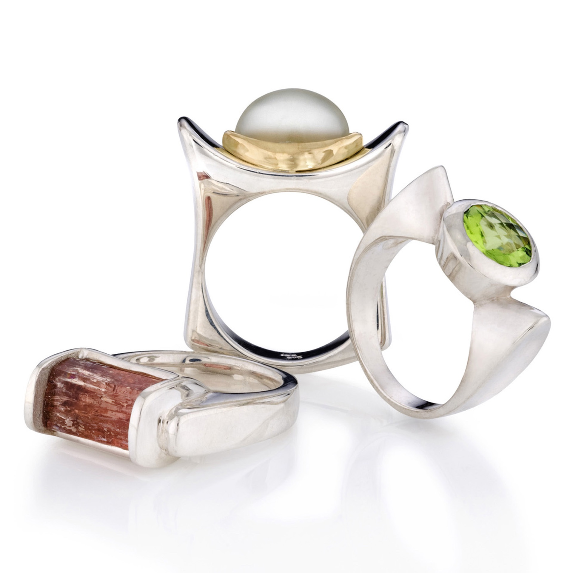 A trio of rings all handcrafted by Kathleen Lynagh Designs, the center ring is a unique statement ring. A solid sterling silver ring showcasing a fin cut moonstone set in an 18kt gold bezel.