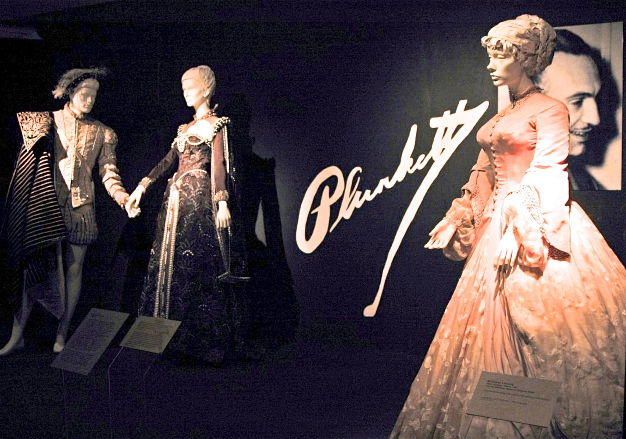"Plunkett Exhibit: Fashion Institute of Design Merchandising – Los Angeles, CA October 31, 2003- July 15, 2004 Pieces shown in Photo: Roger Moore/ Lana Turner, ""Diane"", MGM, 1955, Designed by Walter Plunkett; Elizabeth Taylor, ""Raintree County, MGM, 1947, Designed by Walter Plunkett"