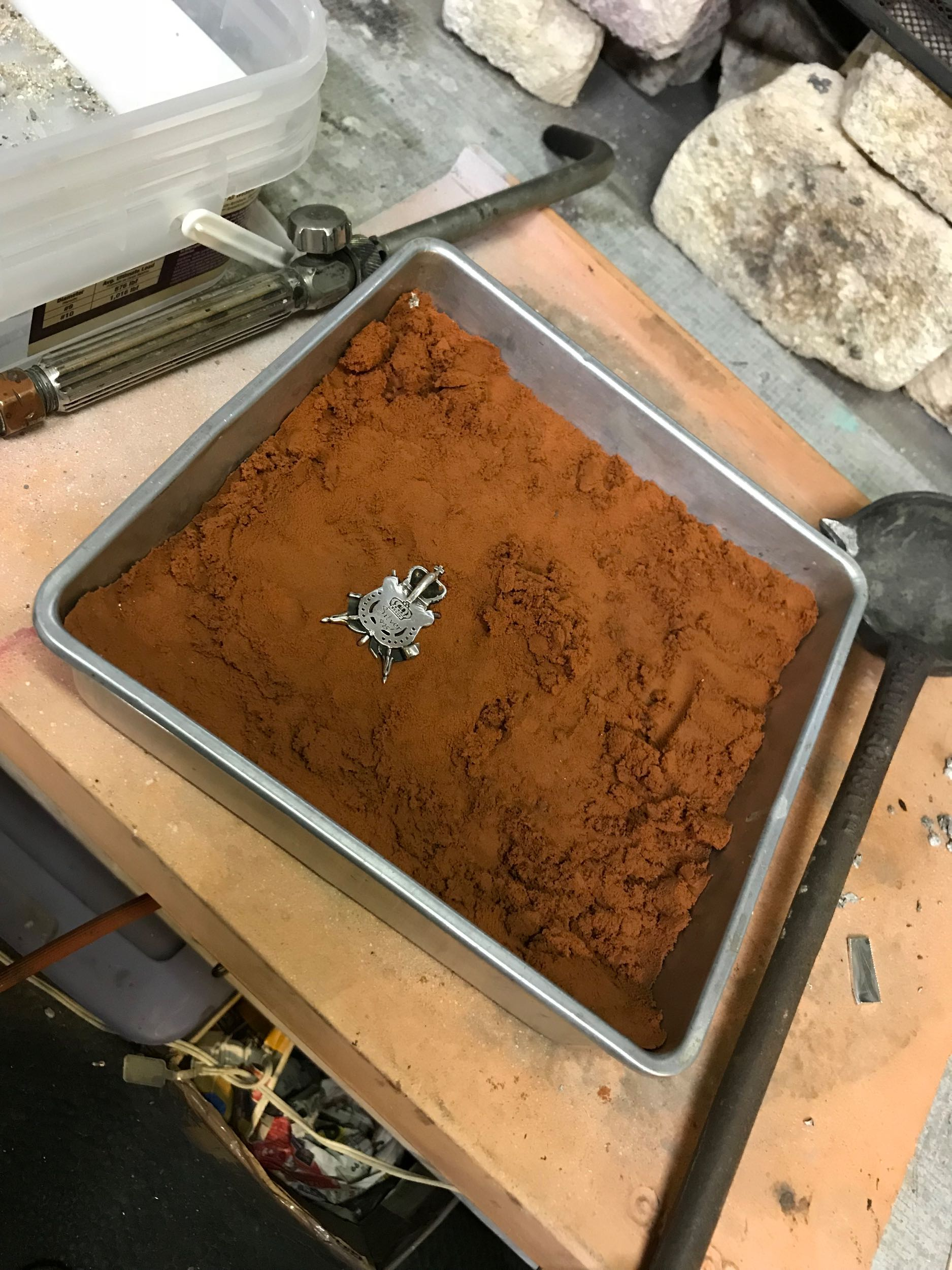 Original brooch placed into the casting sand