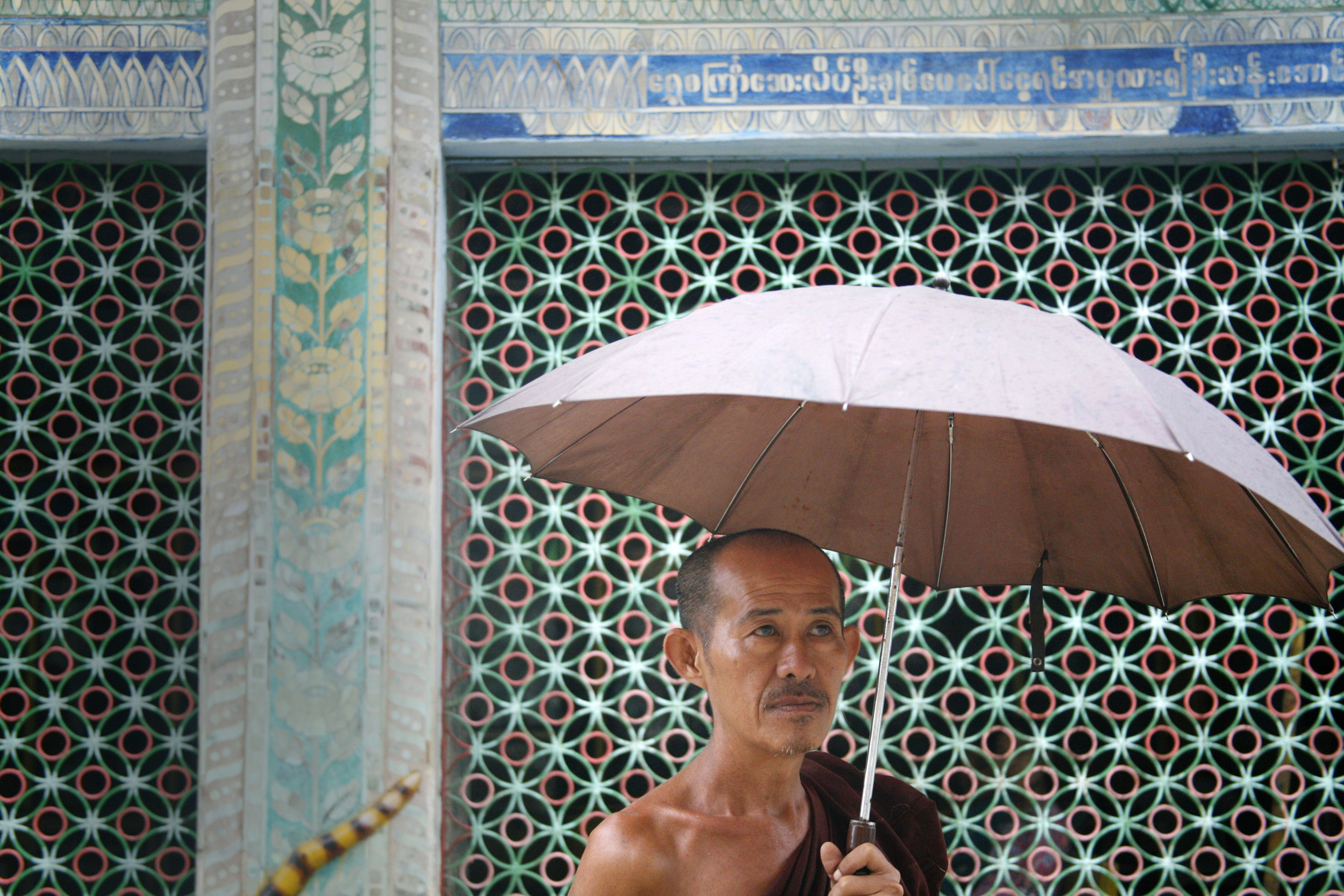 A monk protected himself from sporadic rain showers outside of a temple in Mt. Popa, Myanmar.