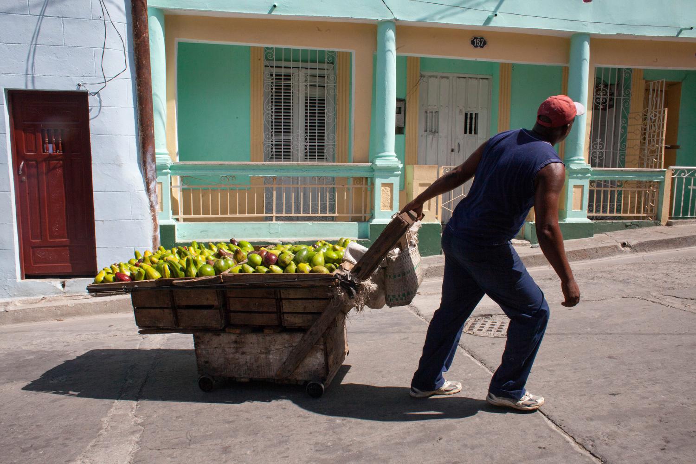A street vendor pulls a fruit cart up a pedestrian walking street in downtown Santiago de Cuba.