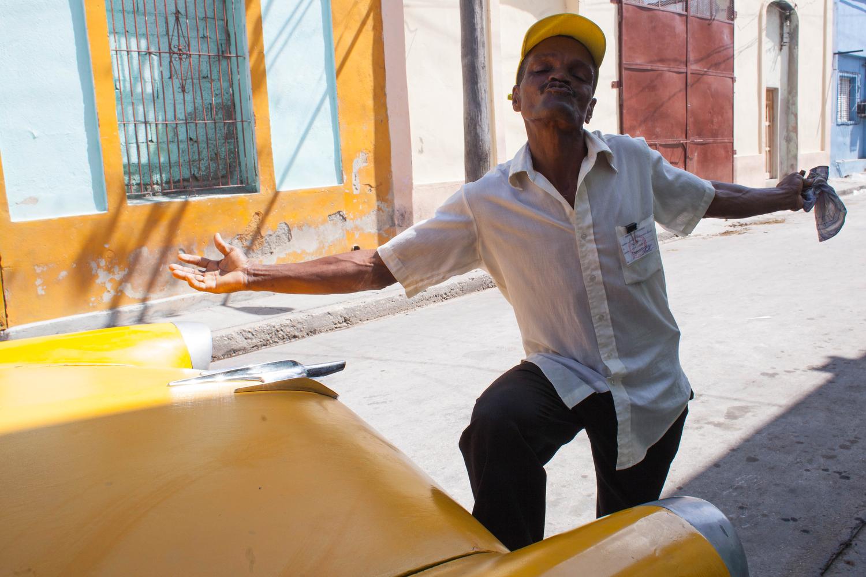 A man sends a kiss, working near the food ration distribution near the port of Santiago de Cuba, Cuba.