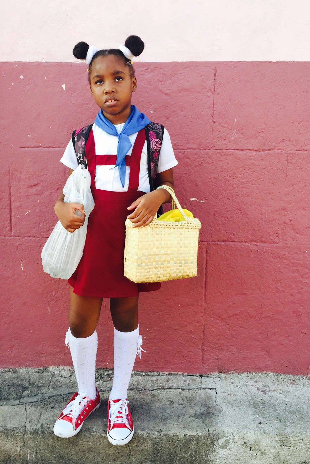 A little girl waits for her mother to walk her to into class in Santiago de Cuba, Cuba.
