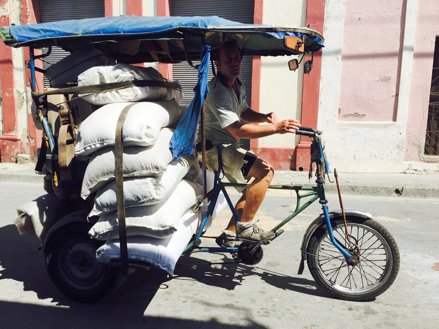 A man transports food rations of rice by bike shipped in from Vietnam for the local people near the port of Santiago de Cuba, Cuba.