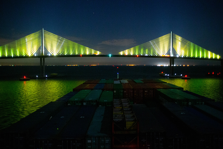 A Chinese container ship guided by Harbor Pilot Carolyn Kurtz glides under the Sunshine Skyway Bridge with a 30-foot clearance.