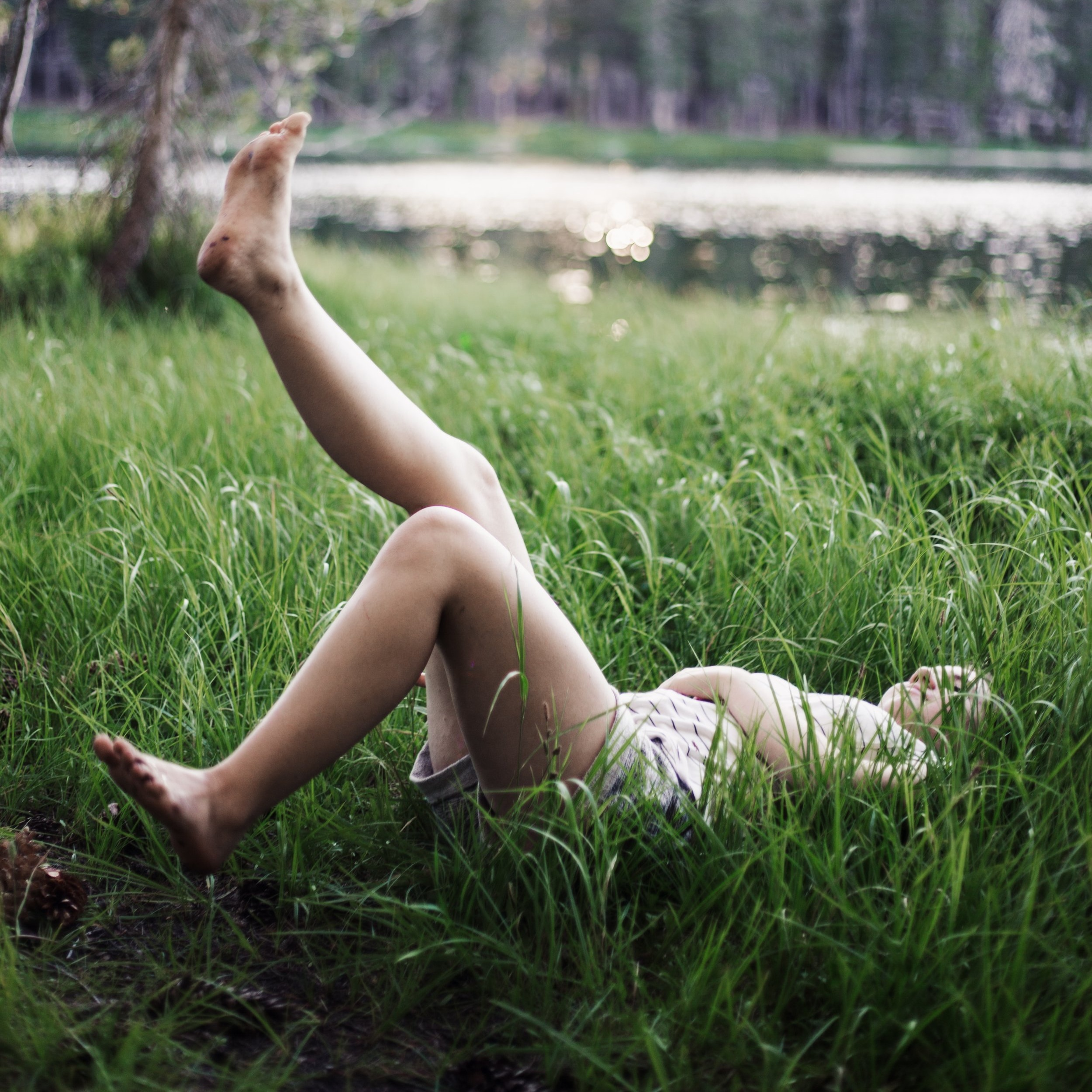 woman+lying+in+the+grass+with+one+foot+in+the+air+looking+relaxed