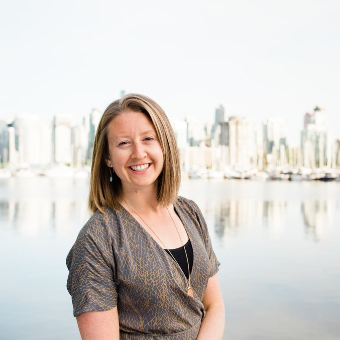 Photo of Renew Retreats founder Danielle Leroux looking at the camera with Vancouver's coal harbour behind her.