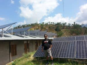 Jevan Baidya standing in front of solar panels.