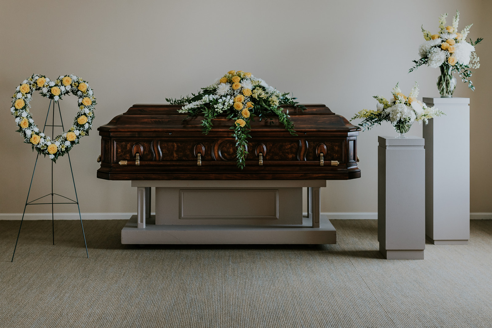 This collection is comprised of five floral pieces: the casket spray, a 24-inch open heart, a compote, vase, and memorial urn arrangement. All of the pieces are designed using yellow roses accented by white flowers such as fugi, hydrangea, and snapdragons. The memorial urn arrangement is constructed in two tiers using three 12-inch wreaths. A clear glass pedestal is provided to elevate the urn, portrait, or keepsake featured in the center wreath.