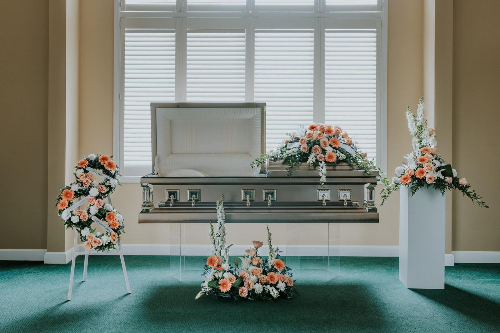 The Honeycomb Collection is arranged using gentle peach tones accented by white and a touch of lavender. Peach gerbera and peach roses are intensified by the white snapdragons, lilies, and carnations.  The collection features five floral pieces: the casket spray, floor arrangement, pedestal arrangement, generations wreath, and memorial urn arrangement. The memorial urn arrangement is designed as one piece but can accommodate two items. The generations wreath can emphasize the importance of family in one's life. Custom designed with three 12-inch wreaths and wrapped with custom printed ribbons, this is truly a memorable piece.