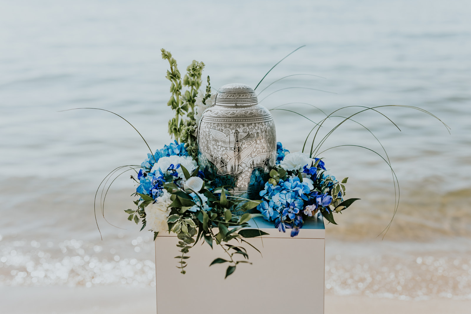 This stand-alone piece is inspired by the Lake Michigan shoreline. Capturing the blue of the water and the green of the dune grass, the memorial urn arrangement is designed using blue hydrangea and delphinium, bells-of-Ireland, ruscus, and bear grass. An accent of shells is added to emphasize the beachscape. Other floral pieces can be designed in this same theme.