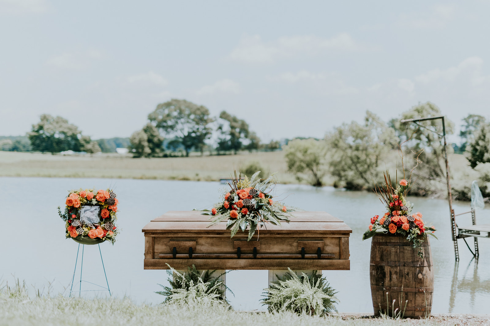 Inspired by the landscape of Moraine Park Farms in Zeeland, this collection captures the love for the outdoors with cattails, pods, grasses, ferns, and willow. The gold and orange tones complement the natural elements used throughout this collection. It's designed using orange roses, red alstroemeria, solidago, carnations, ferns, pods, cattails, and fresh-cut greenery.