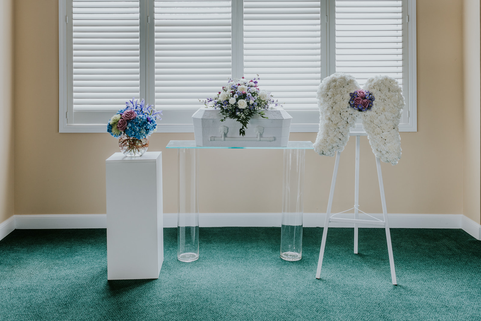 The casket spray of the Celestial Collection is placed on a 24-inch infant casket. It is designed using white roses, purple larkspur, alstroemeria, and aster. The accompanying pieces include custom designed angel wings. This custom easel arrangement uses a form of hand-carved wet floral foam. The wings are created using white carnations accented by a sweet nosegay of lavender roses and purple aster.