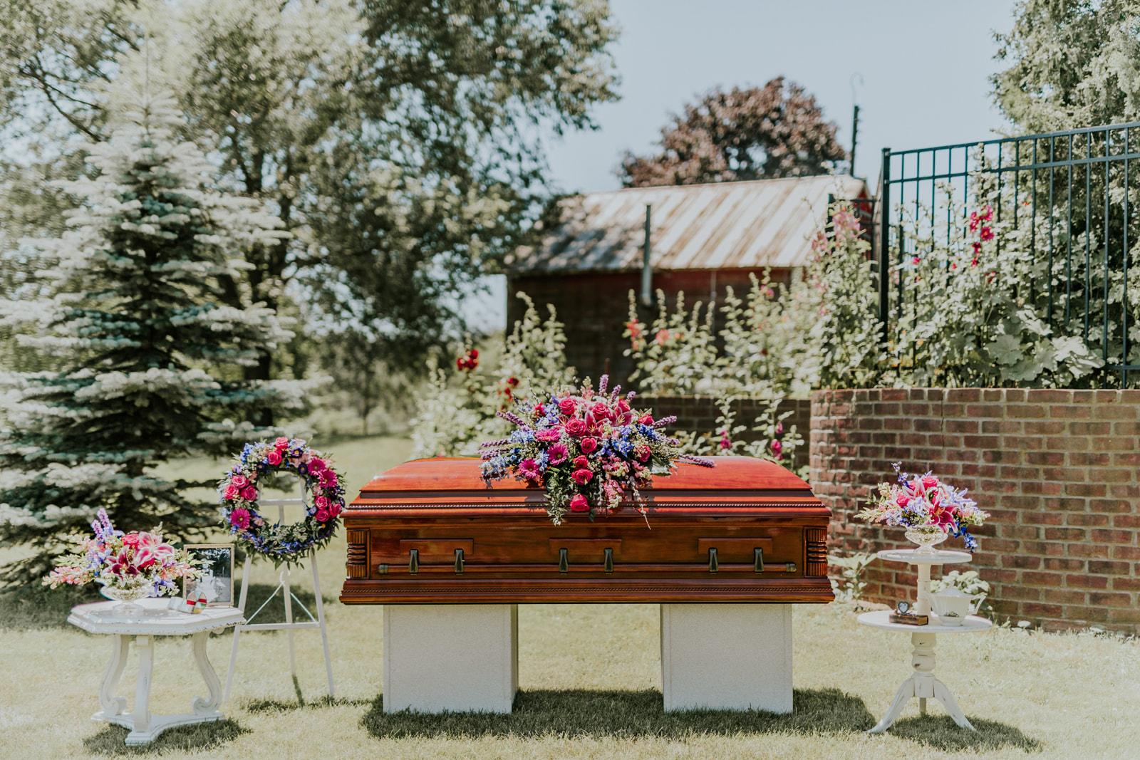 This collection features hot pink roses, stargazer lilies, gerbera, iris, snapdragons, liatris, and blue delphinium. The bright blues, purples, and hot pinks are reminiscent of a spring garden. The collection includes a casket spray, two complementing compotes, an urn arrangement, and a wreath.