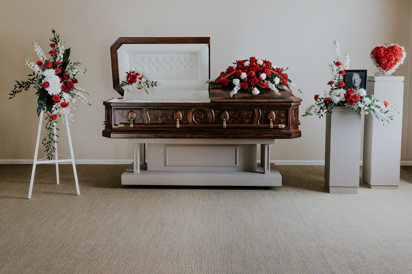 The Heritage Collection offers a traditional approach with its red and white selection of flowers and symmetrically designed casket spray. The complementing floral pieces include a lid piece, easel arrangement, portrait arrangement, 12-inch heart designed in wet floral foam, and memorial urn arrangement.  The flowers included within some or all of the collection pieces are red roses, white orchids, snapdragons, fugi, and carnations.