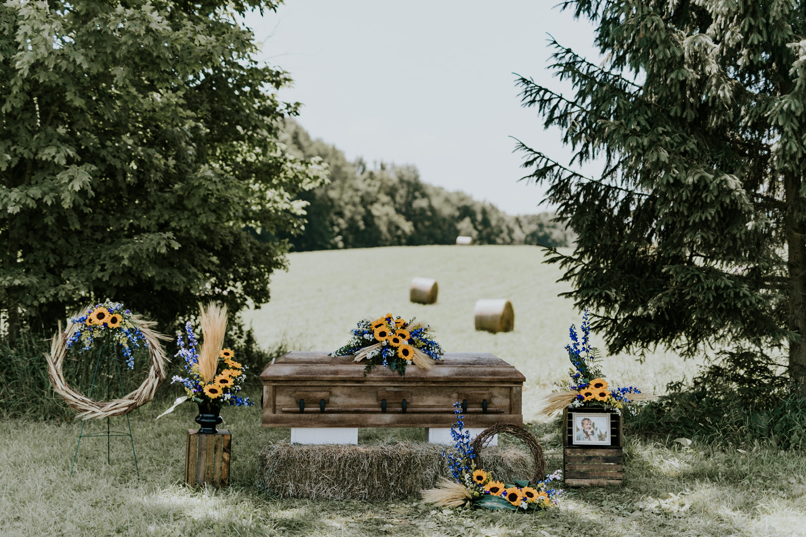 The Bounty Collection derives its inspiration from earth and field, the wheat and sunflowers of late summer accented by the delphinium growing in the garden and aster growing on the path.  The collection is comprised of five floral pieces: the casket spray, a 36-inch grapevine wreath on an easel, a jardiniere arrangement, a pedestal arrangement, and a 24-inch grapevine wreath memorial urn arrangement. All the pieces utilize the elements of wheat, sunflowers, blue delphinium, and aster.