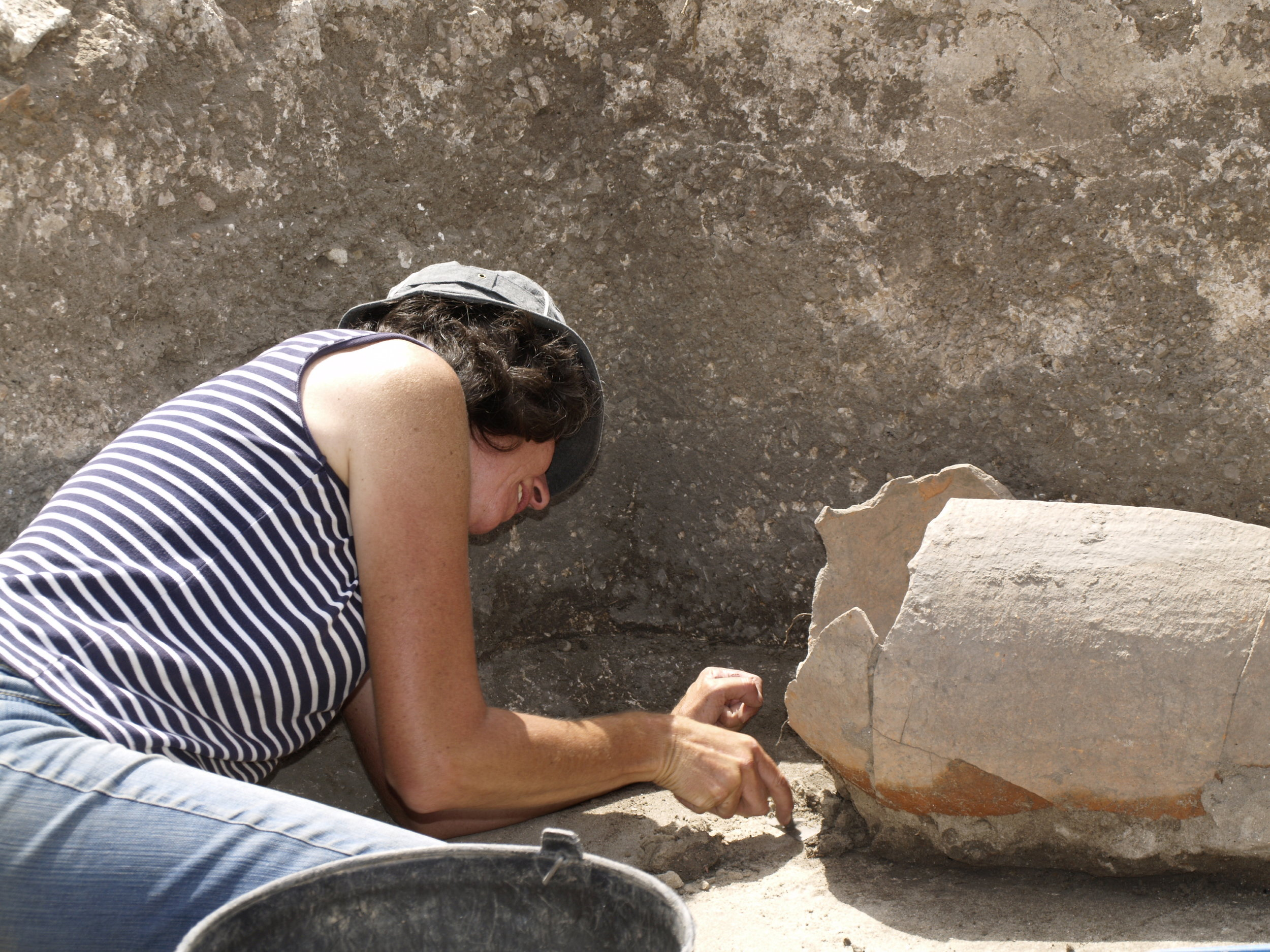 Inês examining a new discovery among the Roman ruins.