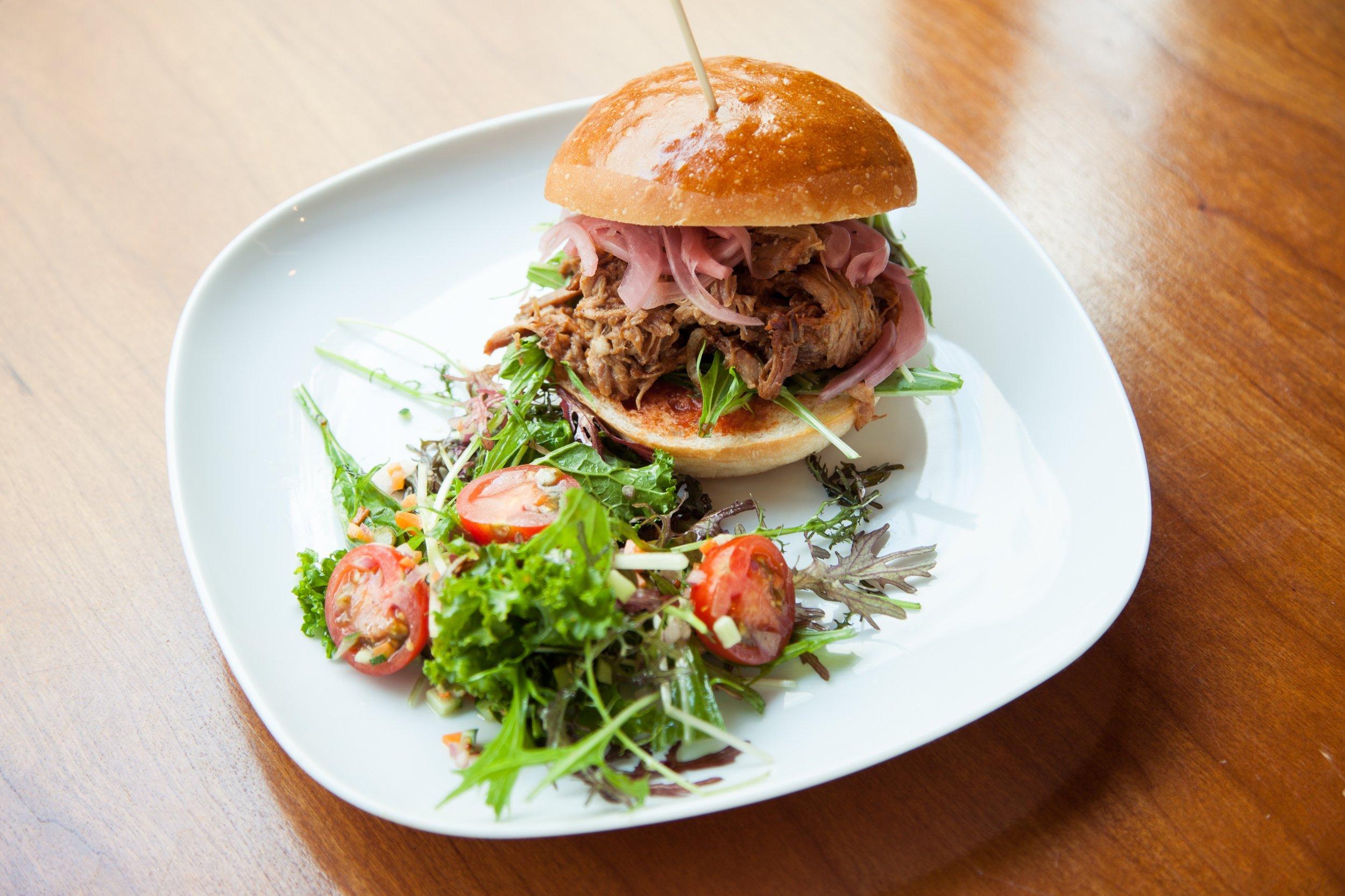 プルドポークサンドウィッチ 紫タマネギピクルス&カーリーフライドポテト。Pulled Pork Sandwich w/ Pickled Red Onion and Side Salad