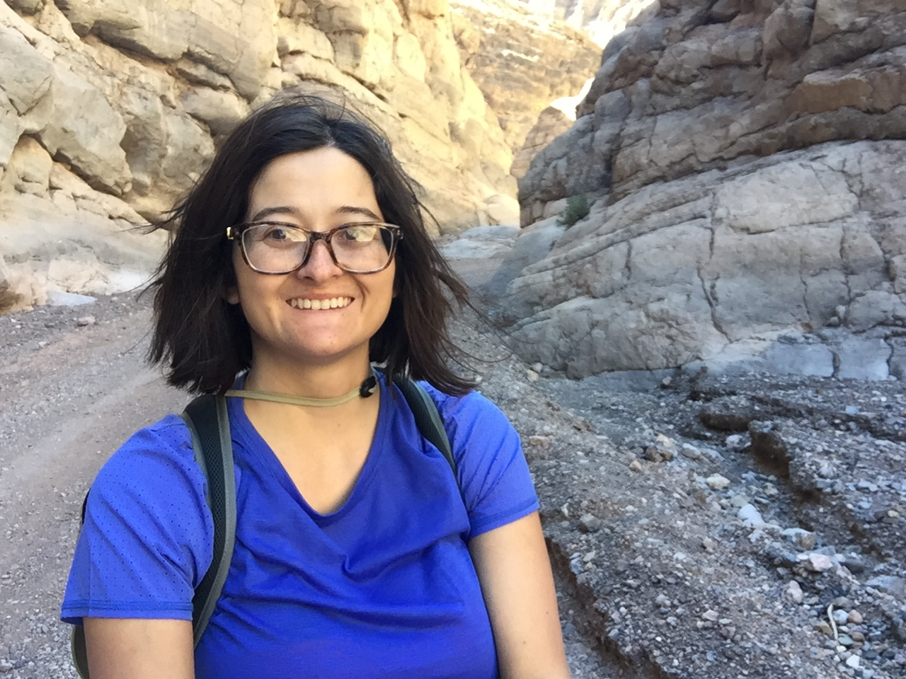 Image Description: A young, smiling, light-skinned Latina woman with dark eyes, glasses, and dark wind-swept shoulder-length hair, wearing a bright blue shirt and a backpack, on a gravel path between huge, craggy stone cliffs.