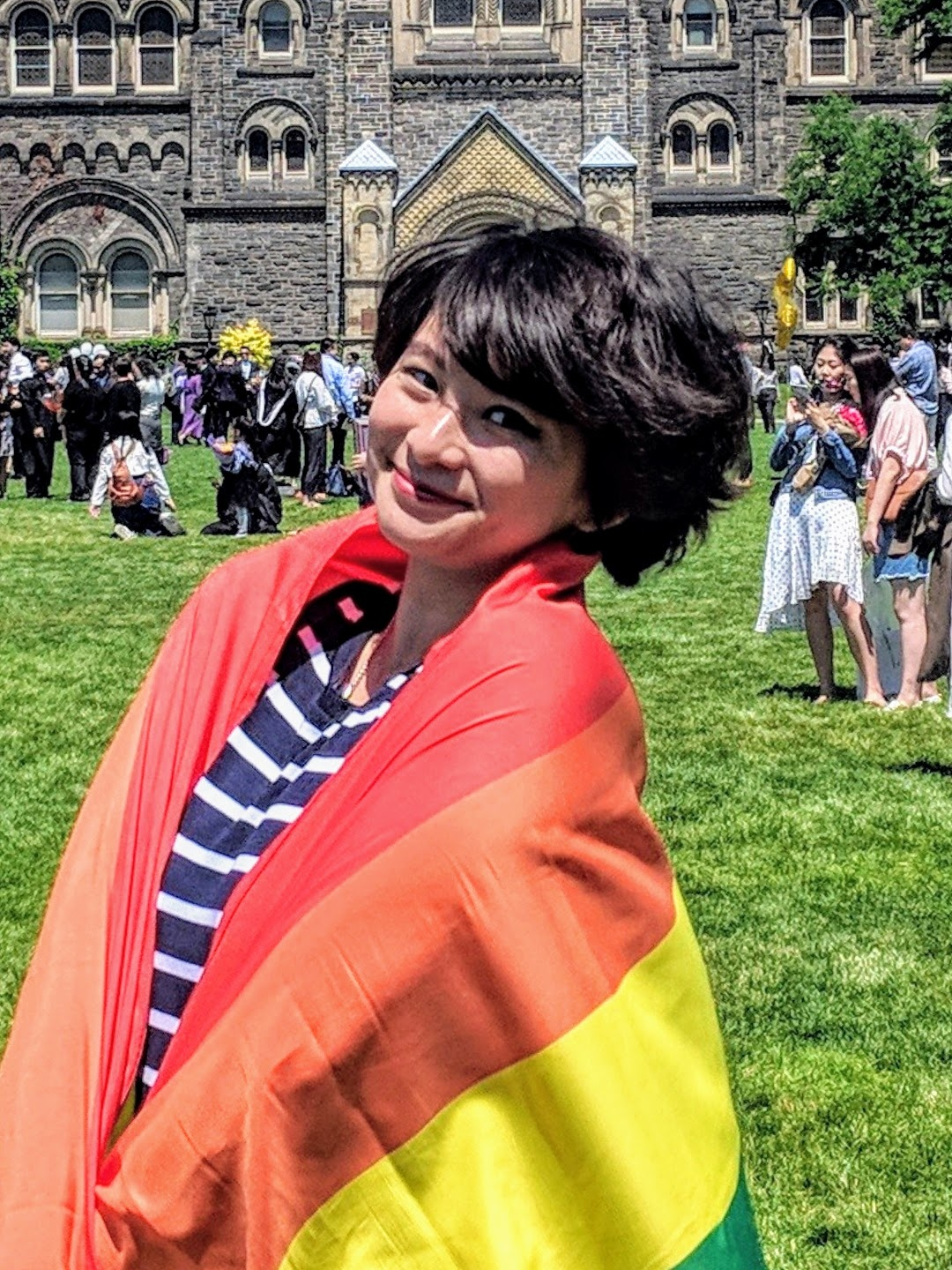 Image Description: A young smiling non-binary East Asian person with medium-length black hair, wrapped in a rainbow pride flag, on a lawn with lots of other people, in front of what looks like a castle .