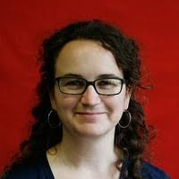 Image Description: A white woman with curly brown hair, glasses and hoop earrings, smiling against a red background.