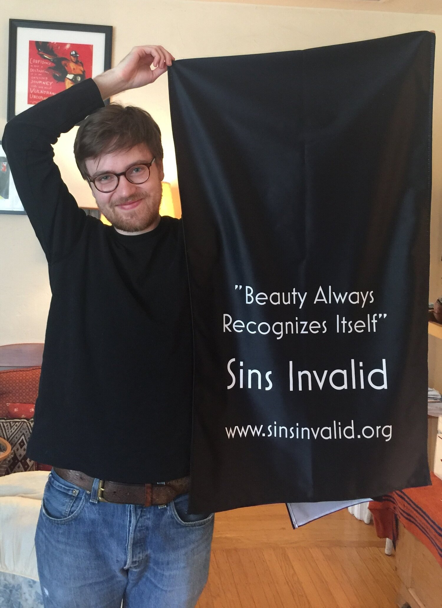 """[Image Description: A white person with brown hair, glasses, and facial hair smiles at the camera, wearing a long-sleeved black t-shirt and jeans, holding up a black banner with white text that reads """"Beauty Always Recognizes Itself - Sins Invalid - www.sinsinvalid.org.""""]"""