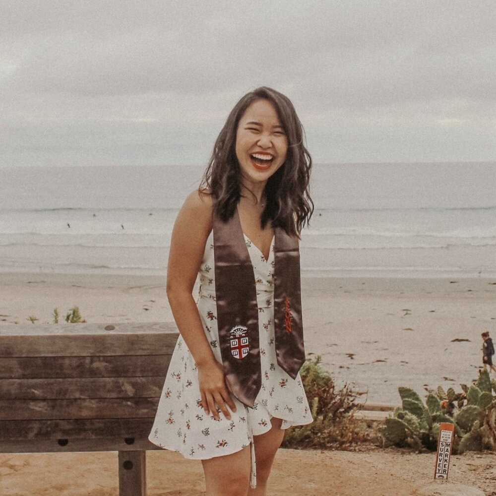[Image Description: A young, light-skinned Asian woman with wavy dark brown hair; a short, white floral dress; and Brown University's graduation stole is laughing with the beach and ocean in the background.]