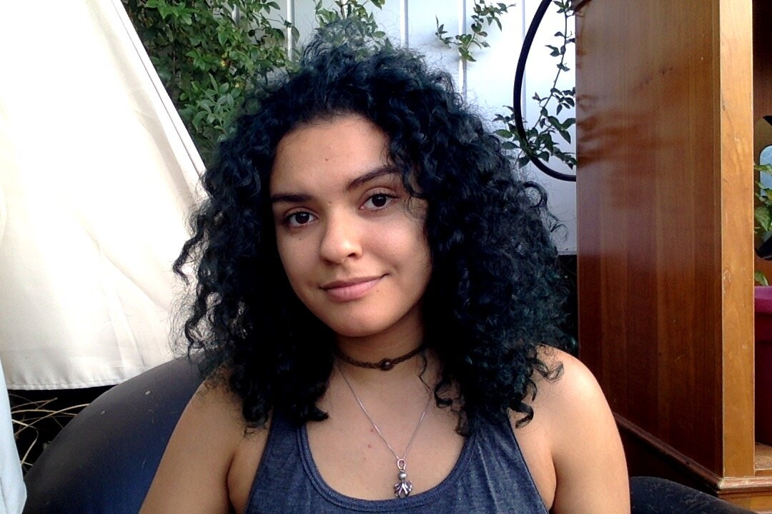 [Image Description: Aa curly haired woman looking at the camera with a small smile, sitting outside with wooden furniture and and leafy vines in the background.]