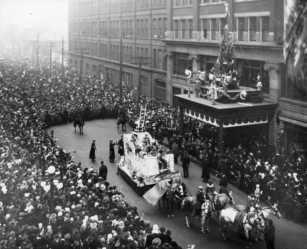 Santa climbing the ladder from a float to the Eaton's department store during the 1918 Eaton's Santa Claus Parade in Toronto.