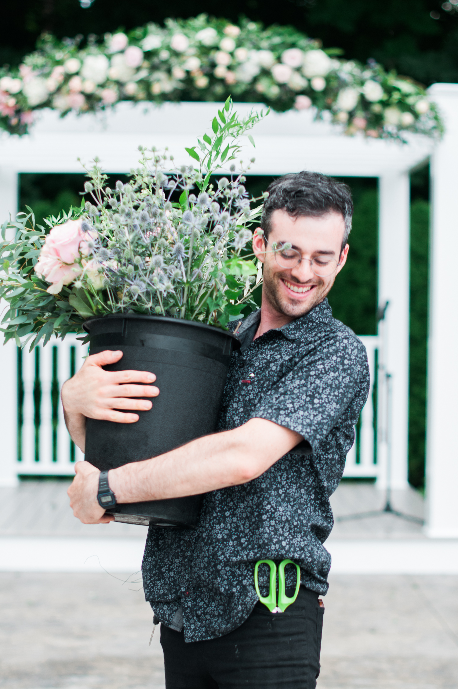 Ephemera Designs employee holding bucket of flowers & greenery