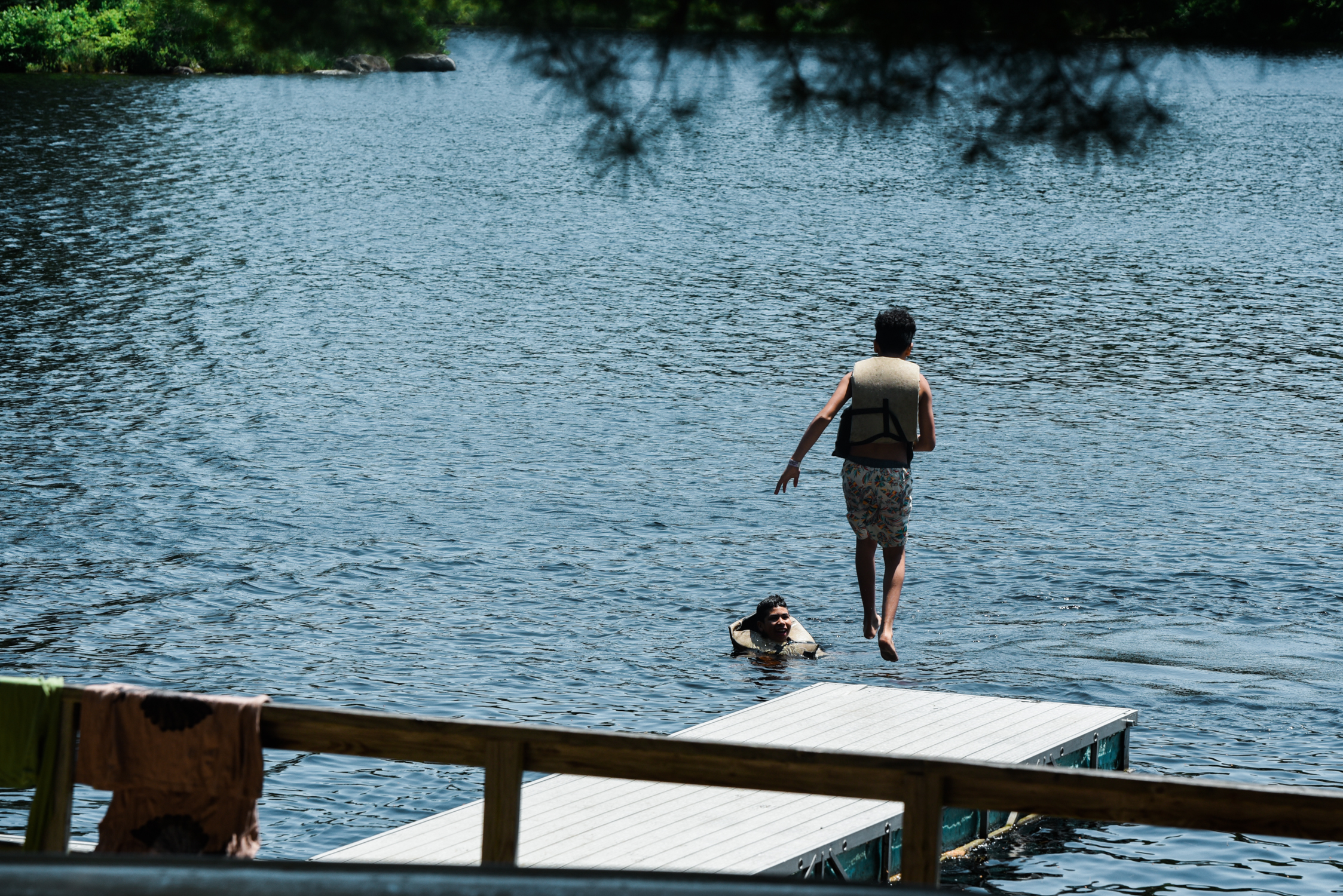 ephemera designs photography unifier festival - person jumping off dock into water with friend
