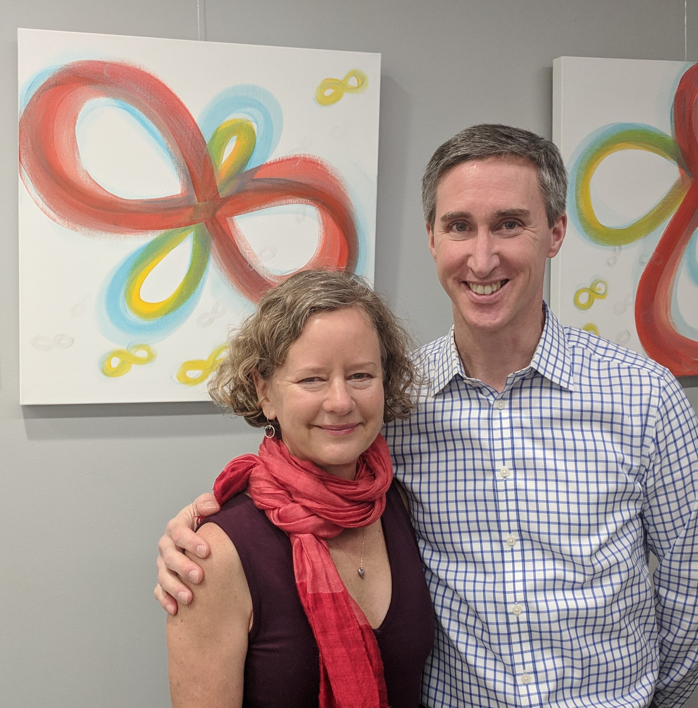 Karin with Dr. Ruff in front of some of her healing art as flying infinities