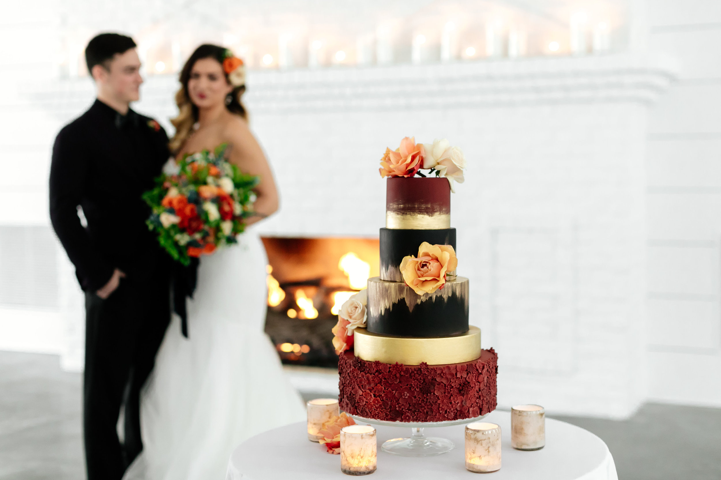 Rich fiery wedding cake design. Maroon bas relief floral and gold painted details over black and huge roses to accent. Captured by  Leah Fontaine Photography .