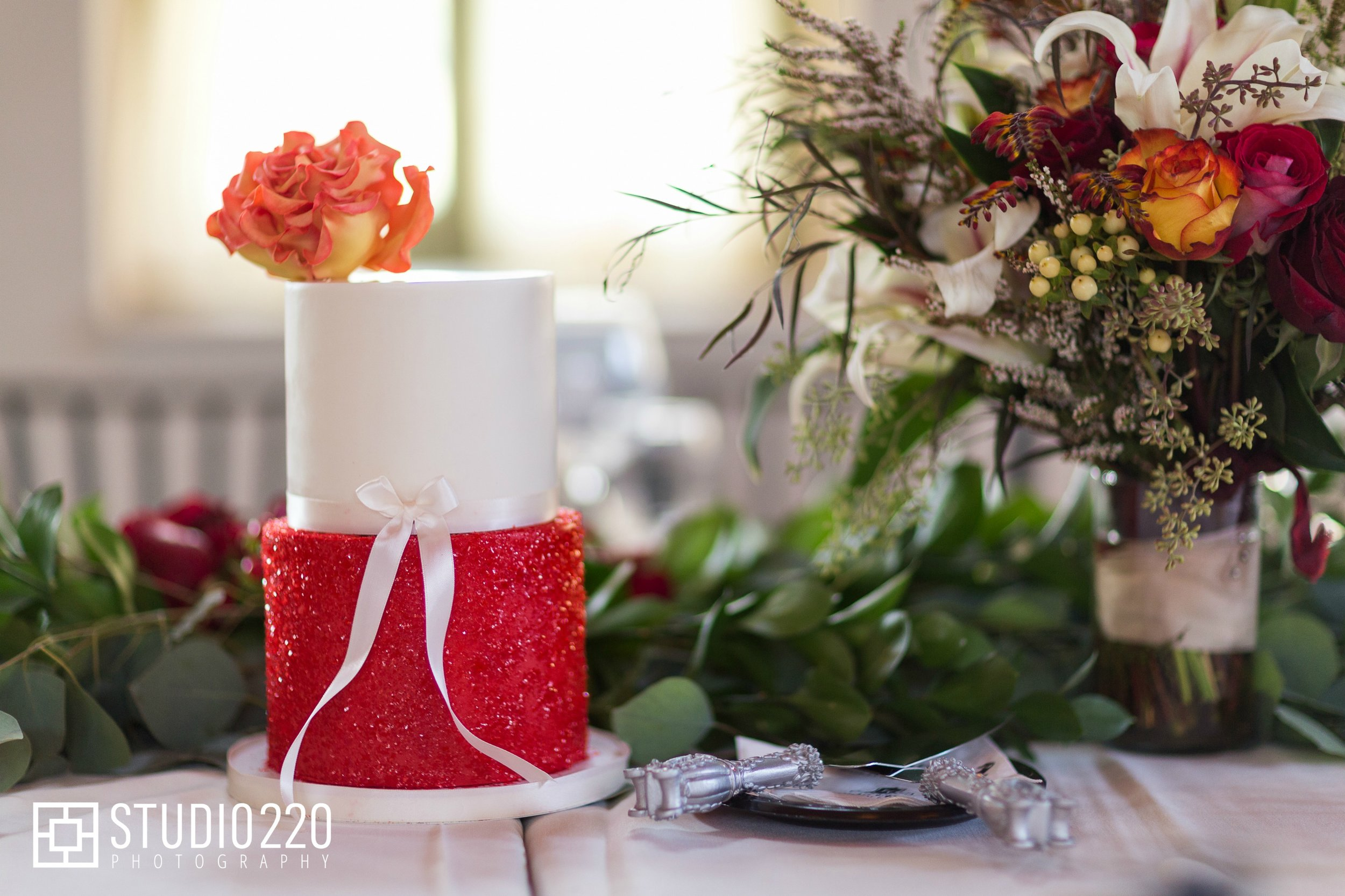 Two-tier wedding cake featuring a sparkly red base and a fire rose made from sugar paste. Captured by  Studio 222 Photography .