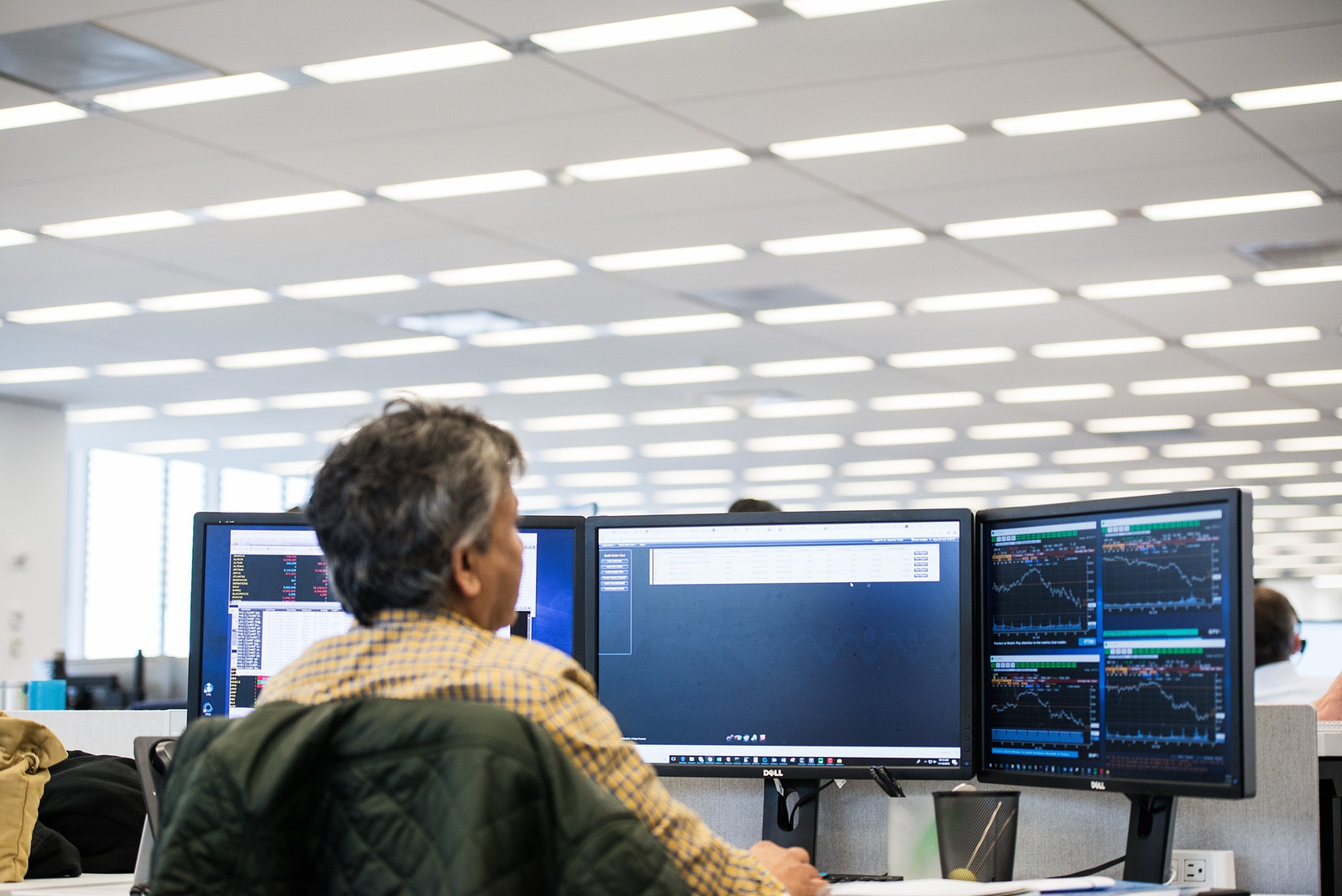 Liquidnet technologist analyzing market intelligence in front of three monitors
