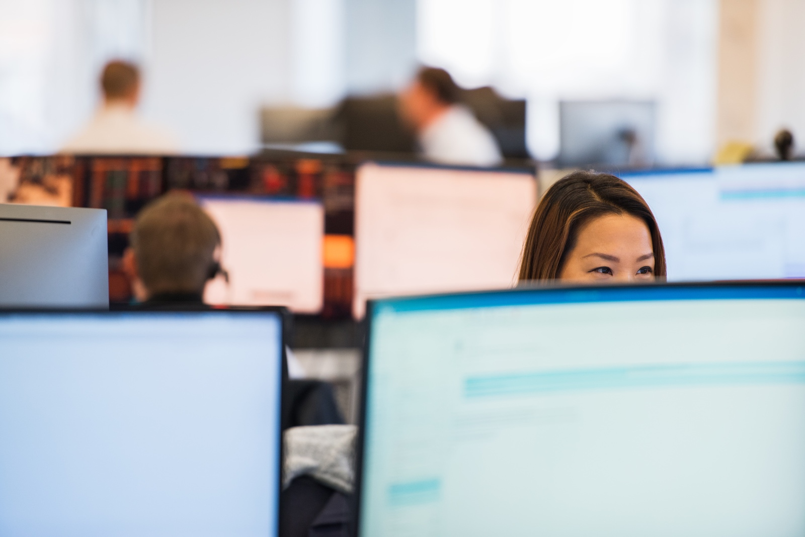 Liquidnet employee sitting at workstation with bottom half of face concealed by row of monitors