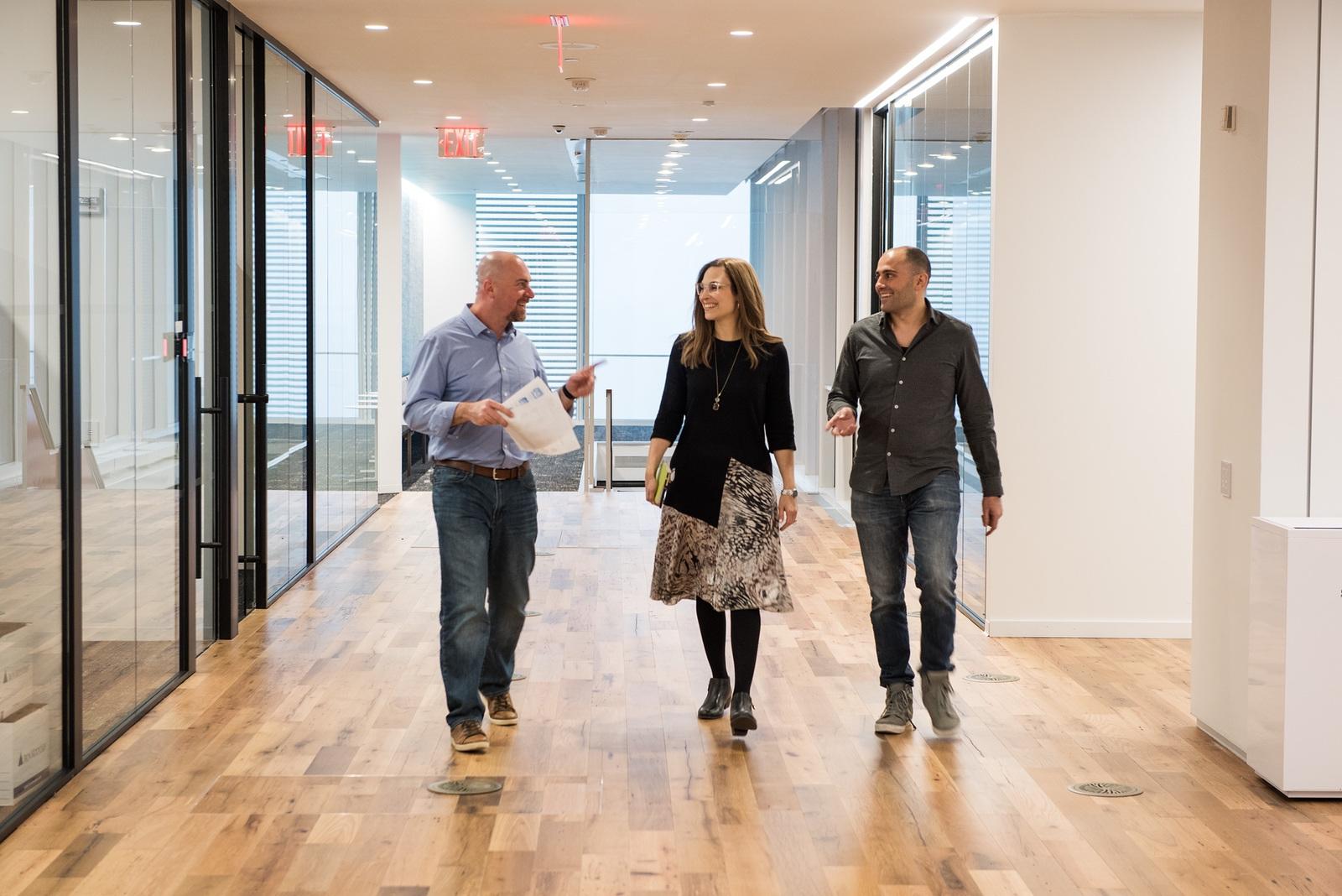 Three Liquidnet employees walking down hallway