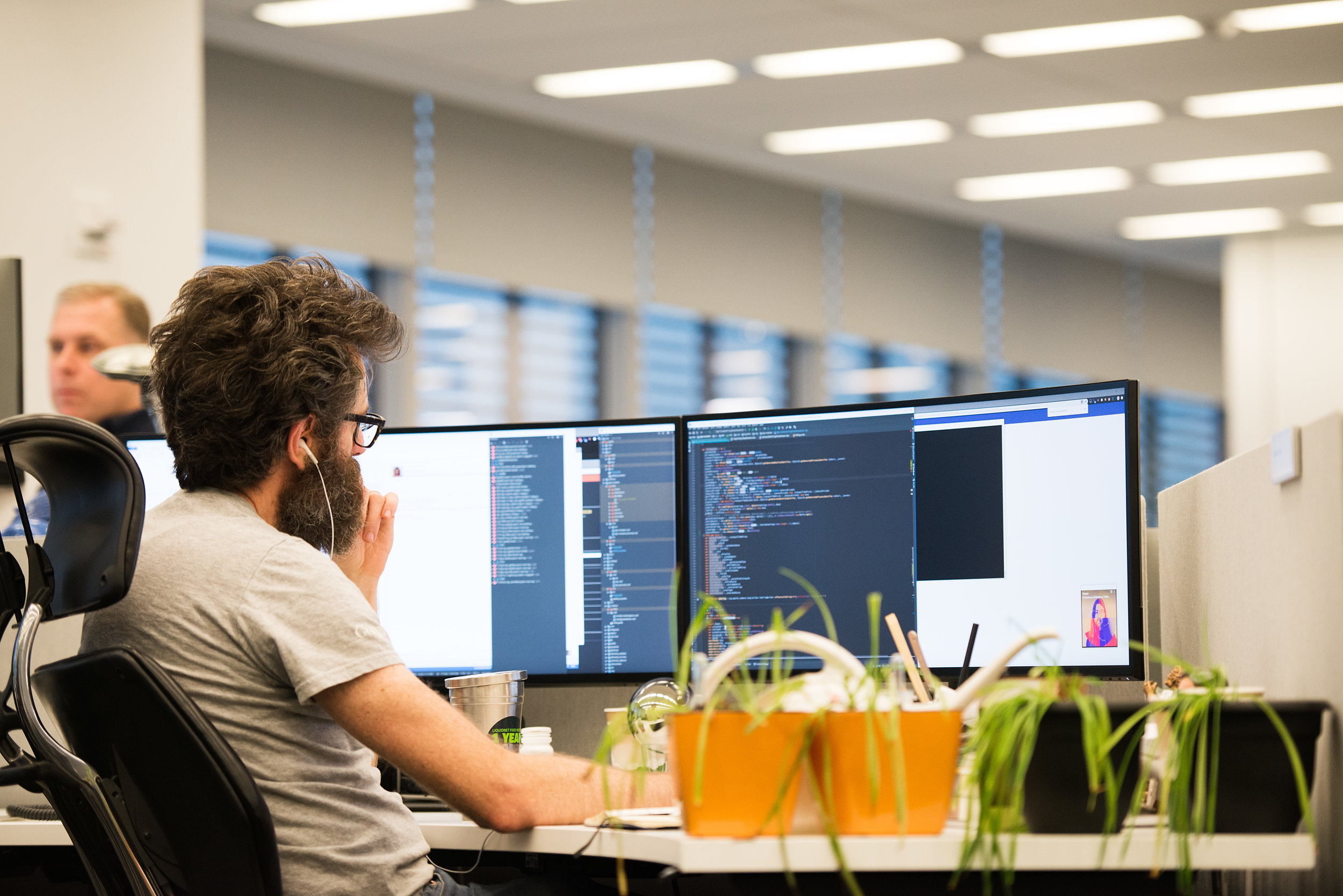 Liquidnet technologist works on market surveillance code at desk with potted plants
